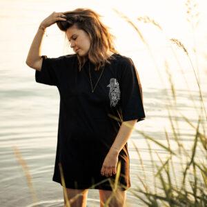 Dame mit T-Shirt Kleid steht im Wasser